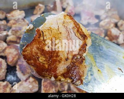 Pork tenderloin steak, on a spatula, infront of more pork steaks - Stock Photo