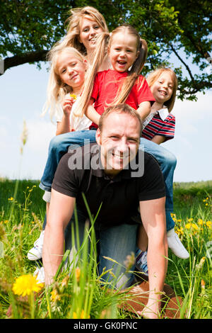 family riding on dad - Stock Photo