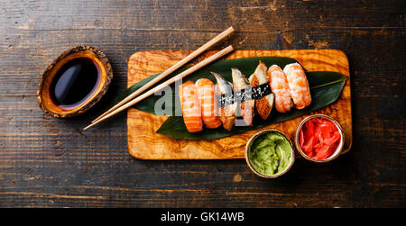 Nigiri Sushi Set on bamboo green leaf on olive wood board with soy sauce on wooden background - Stock Photo
