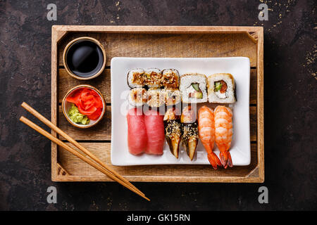 Sushi Set nigiri and rolls with chopsticks, ginger, soy sauce and wasabi in tray on dark background - Stock Photo