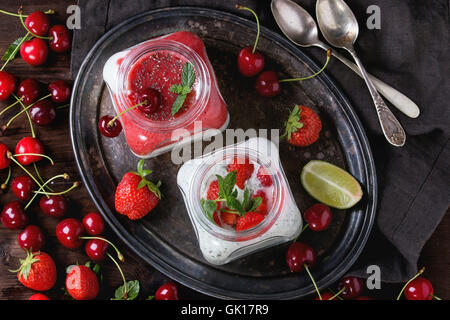 Two Square glass jars with homemade yogurt with mint, strawberry puree, cherry and chia seeds served on vintage - Stock Photo