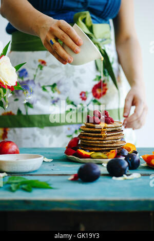 Girl with flower apron pours honey over pancakes - Stock Photo