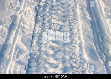 The road in the snow on a snowmobile at sunset and trails - Stock Photo