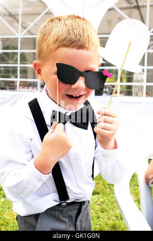Young lad at a wedding reception,holding a pair of paper spectacles over his eyes. Dressed in a morning suit, with - Stock Photo