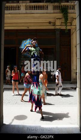 A clown walking on stilts in old Havana, Cuba. - Stock Photo