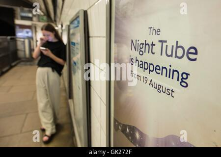A passenger stands near an advert for the night tube on a platform at Oxford Circus underground station, in London, - Stock Photo