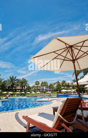Lounge chair and parasol at the swimming pool. Palm Garden Beach Resort, Hoi An, Quang Nam Province, Vietnam. - Stock Photo