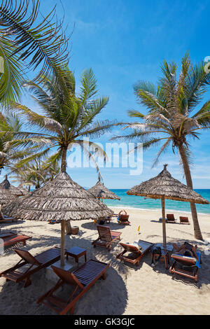 Lounge chairs under thatched parasols on Cua Dai Beach. Hoi An, Quang Nam Province, Vietnam. - Stock Photo