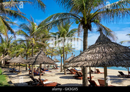 Thatched parasols under coconut palm trees on Cua Dai Beach. Hoi An, Quang Nam Province, Vietnam. - Stock Photo
