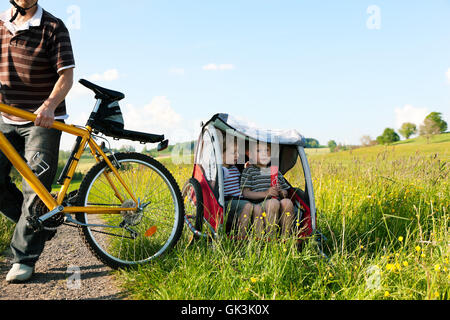 family rides a bike in the summer with trailer - Stock Photo