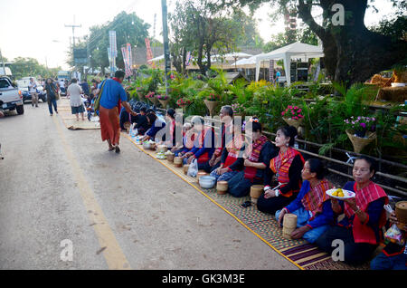 Phu tai people preparing food and almsgiving with sticky rice for put food offerings to monks procession at the - Stock Photo