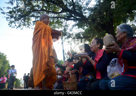 Traditional of almsgiving with sticky rice by Monks procession walk on the road for people put food offerings on - Stock Photo