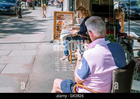A young woman and an older man enjoying dining alfresco in London on a beautiful sunny day - 8th August 2016 - Stock Photo