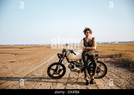 Young brutal man in black leaning on a motorcycle - Stock Photo