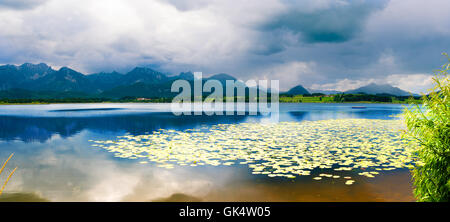 Forggensee Mountain Lake in the south of Bavaria, Germany and the mountains on horizon - Stock Photo