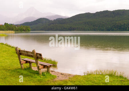 Bench by the lake  in the south of Bavaria, Germany and the mountains on horizon - Stock Photo