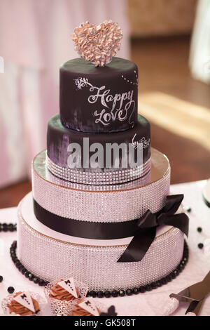 Decorated chocolate wedding cake with brown ribbon - Stock Photo