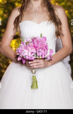 Beautiful pink peony wedding bouquet in bride's hands, closeup