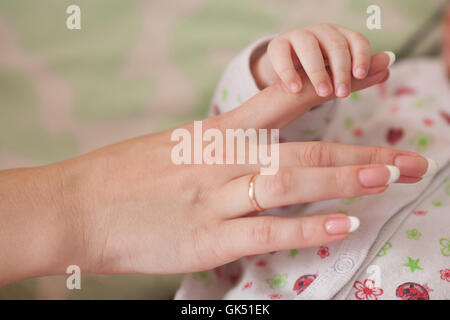 Son and mother, baby holding moms finger. Family concept - Stock Photo