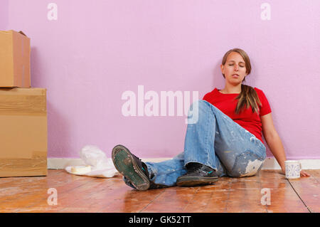 young pretty woman sitting in the apartment on the floor and takes a break from renovi - Stock Photo