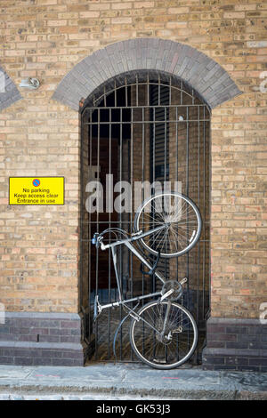 A bicycle is locked to a gate despite a no parking warning sign near by - Stock Photo