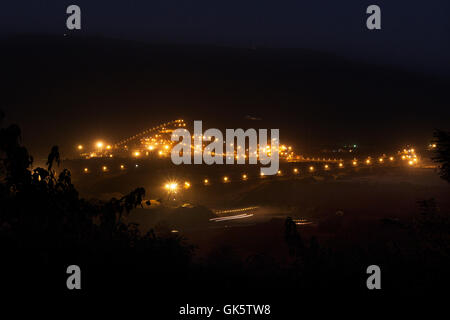 Mining operations for transporting and managing iron ore. Wide view at night new mine processing plant lit up and - Stock Photo