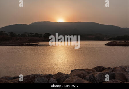 Mining operations for producing and managing iron ore. Sunset over reservoir dam built for new water resource for - Stock Photo