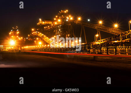 Mining operations for transporting and managing iron ore. Night view of new mine processing plant lit up and illuminated - Stock Photo