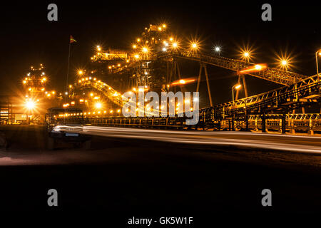 Mining operations for transporting and managing iron ore. Night view of new processing plant lit up and illuminated - Stock Photo