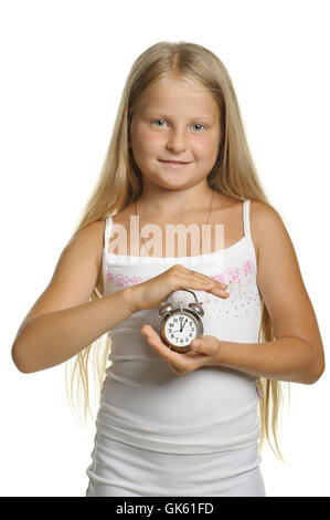 The girl holds an alarm clock in hands - Stock Photo
