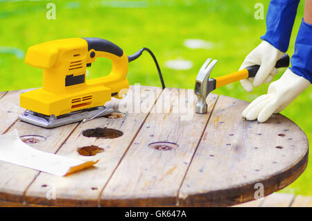 hands holding a hammer over a table next to a electric sander. - Stock Photo