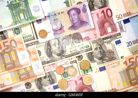 Dollars, Euro and Yuan banknotes and coins background - Stock Photo