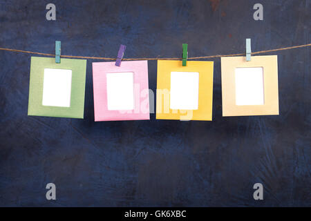 Four frames hanging on rope on blue background Stock Photo ...