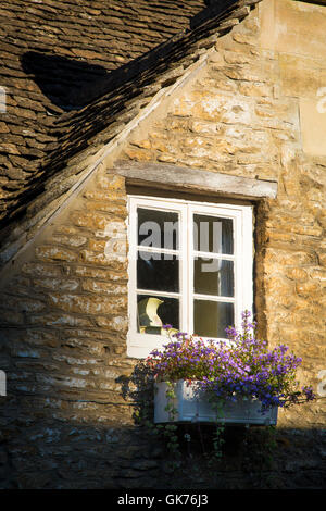 Window and flower box on a cottage home in Castle Combe, the Cotswolds, Wiltshire, England, UK - Stock Photo