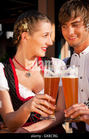 couple in tracht drinking wheat beer - Stock Photo