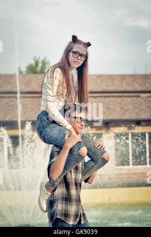 Sweethearts teenagers. Girlfriend and boyfriend together. They wear glasses. Warm toning. The boy put the girl on - Stock Photo