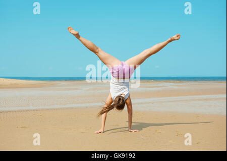 Beautiful energetic young woman doing handstand on the beach - Stock Photo