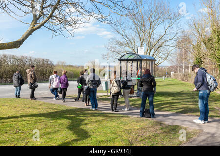 Young people queuing at a bus stop in the countryside, Nottinghamshire, England, UK - Stock Photo