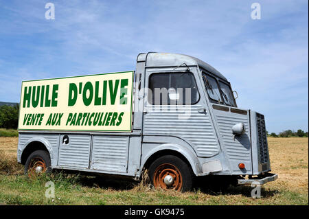 Old French truck with advertisement board with text: Olive oil for sale to private individuals - Stock Photo