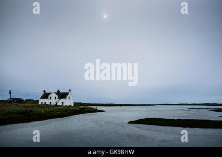 Remote croft by a loch in North Uist, outer Hebrides - Stock Photo