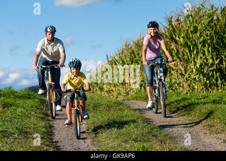 family rides a bike in the summer - Stock Photo