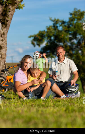 family makes a bike ride - Stock Photo