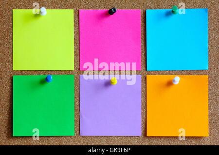 colorful sticky notes on cork bulletin board - Stock Photo