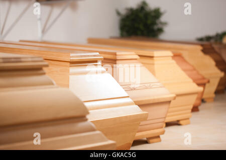 coffins in a store at a funeral - Stock Photo