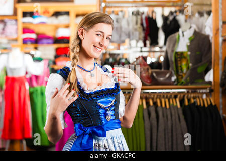 woman tasting tracht or dirndl in a shop at - Stock Photo