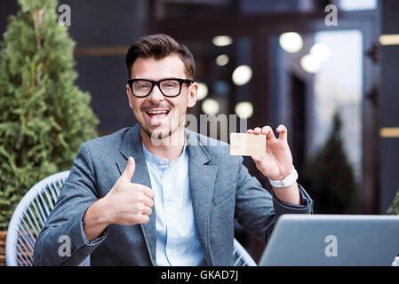 Overjoyed man holding gold card - Stock Photo