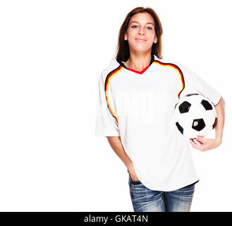 laughing young woman in football shirt with football under his arm - Stock Photo