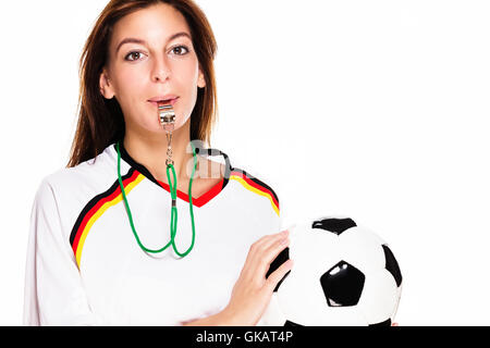 young woman with a whistle holding football - Stock Photo