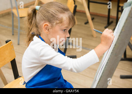 Five-year girl paints on an easel in the drawing lesson - Stock Photo