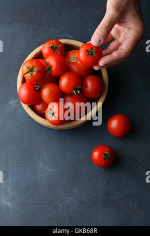 Tomatoes in wood bowl, food background - Stock Photo